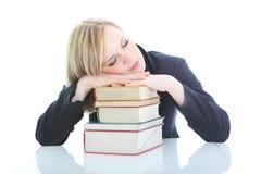 Trött blond kvinna som sovar på böcker Royaltyfri Foto