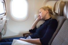 Trött blond tillfällig caucasian kvinna som ta sig en tupplur på flygplanet Fotografering för Bildbyråer