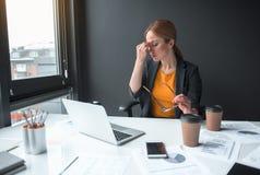 Trött dam som har jobb med anteckningsbokdatoren arkivbild