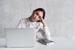 Trött dam som sover på arbetsplatsen royaltyfri foto