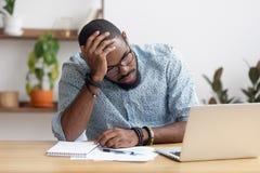 Trött deprimerad uttråkad afrikansk affärsman som är frustrerad vid affärsfel royaltyfri bild