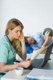 Trött doktor som gör skrivbordsarbete arkivfoton