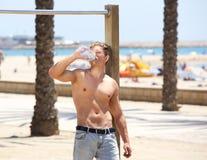 Trött dricksvatten för ung man för kondition efter genomkörare Arkivbilder