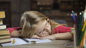 Trött flicka för blont hår som hemma sover på skrivbordet arkivfilmer
