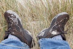 Trött fot i smutsiga fotvandra skor efter en vandring i sanddyn Arkivbilder