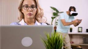 Trött freelancerkvinna som arbetar på datoren, medan hennes pojkvän gör oväsen i bakgrunden lager videofilmer