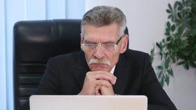 Trött gammal affärsman som arbetar med en dator i ett modernt kontor stock video