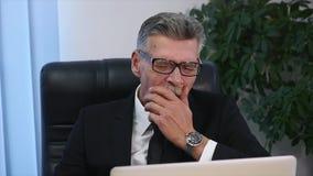 Trött gammal affärsman som arbetar med en dator i ett modernt kontor arkivfilmer