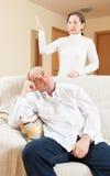 Trött grabb som lyssnar till hans ilskna kvinna Arkivfoton