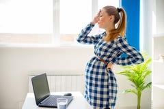 Trött gravid kvinna som i regeringsställning arbetar royaltyfria foton