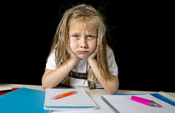 Trött gullig yngre skolflicka med sammanträde för blont hår i spänningen som arbetar göra läxa som ser borrad royaltyfri bild