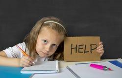 Trött gullig yngre skolflicka med sammanträde för blont hår i spänningen som arbetar göra läxa som ser borrad royaltyfria foton