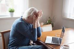 Trött hög man som lider från huvudvärken som masserar ögon arkivbild