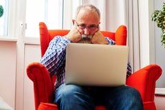 Trött hög man som ser bärbara datorn Arkivfoto