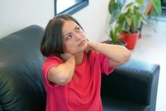 Trött hals Kvinnalidande från hals smärtar hemma på soffan En avkänning för kvinna` s av trötthet, utmattat som är stressad royaltyfri foto