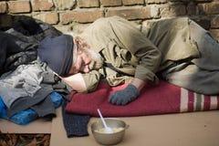 Trött hemlös gamal man som sover på papp i gatan royaltyfria bilder