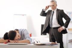 Trött kontorsarbetare som ligger hennes huvud på händer fotografering för bildbyråer