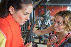 Trött kvinna med instruktören som övar på gradvist i idrottshall royaltyfri bild