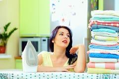 Trött kvinna, når stryka kläder, hemmiljö royaltyfri fotografi
