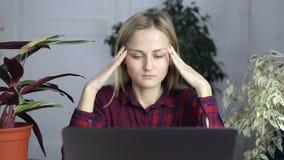 Trött kvinna och att massera hennes huvud som avlöser spänning från lång tid av arbete och ser en bärbar datorskärm stock video