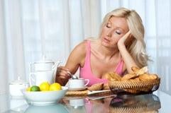 Trött kvinna på frukosten royaltyfria bilder
