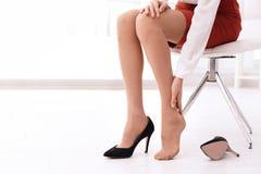 Trött kvinna som av tar skor på kontoret arkivfoton