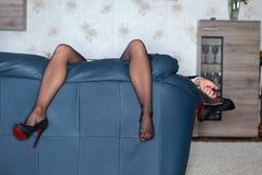 Trött kvinna som hänger höga häl efter parti arkivfoto