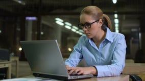 Trött kvinna som i regeringsställning kontrollerar tid på klockan, arbetande overhours att möta stopptid lager videofilmer