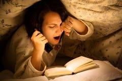 Trött kvinna som läser en bok arkivbilder