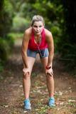 Trött kvinna som tar ett avbrott, medan jogga Royaltyfria Foton