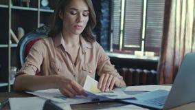 Trött kvinnaaffärsanalytiker som i regeringsställning arbetar med dokument på aftonen lager videofilmer