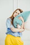 Trött kvinnahållkudde Flickan utan makeup önskar att sova Fotografering för Bildbyråer