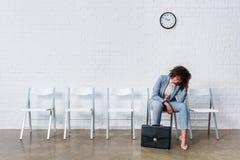 Trött kvinnlig kandidat med att vänta för portfölj Arkivbild