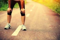 Trött kvinnlig löpare som tar en vila, når att ha kört royaltyfria foton