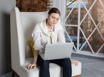 Trött kvinnlig yrkesmässig författare som läser hennes artikel på netto-boken under lång hårt arbetedag arkivbilder