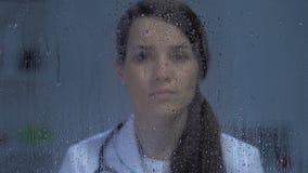 Trött kvinnligt doktorsanseende nära regnigt fönster efter kirurgi, tålmodig död arkivfilmer