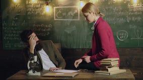 Trött lärare och kvinnlig student som sitter på tabellen för att meddela och lösa problem Tankfull ung professor och stock video