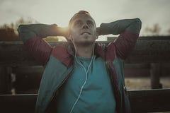 Trött löparesammanträde som kopplar av och lyssnar till musik din telefon, ögon stängde sig på en träpir, sport Arkivfoton