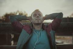 Trött löparesammanträde som kopplar av och lyssnar till musik din telefon, ögon stängde sig på en träpir, sport Royaltyfri Bild