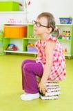 Trött liten flickasammanträde på bunt av böcker Arkivbild