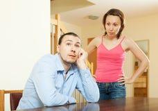 Trött man som lyssnar till hans ilskna kvinna Arkivbild