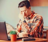 Trött man som sitter över bärbara datorn Royaltyfria Foton