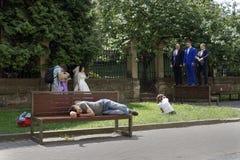 Trött man som sover på en bänk medan fotograf som tar bilder för att gifta sig processionen arkivfoto