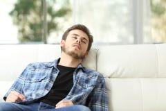 Trött man som sover på en soffa royaltyfri foto