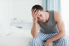 Trött mansammanträde på hans säng royaltyfri foto