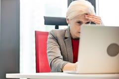 Trött mogen affärskvinna som i regeringsställning använder bärbara datorn på skrivbordet arkivfoton