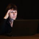 Trött mogen kvinna som sent arbetar på datoren på ni Arkivbild