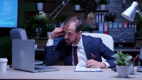 Trött och överansträngd affärsman sent på natten i kontoret arkivfilmer