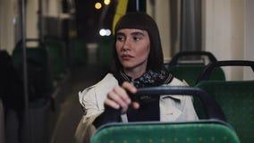 Trött och deprimerad ung kvinna som bara sitter nära transportfönstret och tänka av något stadslampor lager videofilmer