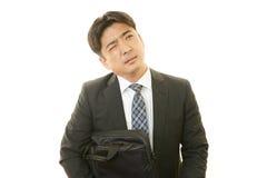 Trött och stressad asiatisk affärsman royaltyfria bilder